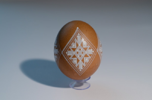 Brown egg with white ink geometric pattern